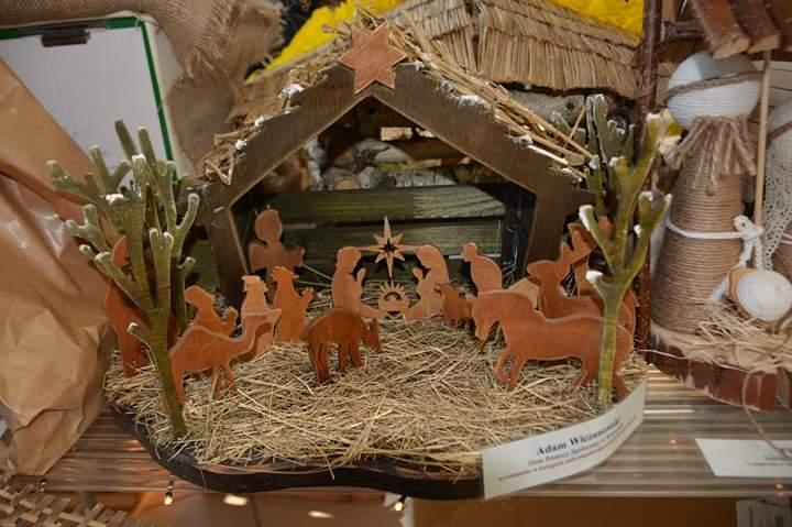 Drewniana szopka Bożonarodzeniowa. Drewniana szopka ze słomą w środku. Z drewna wycięte zwierzęta oraz postacie Święte.