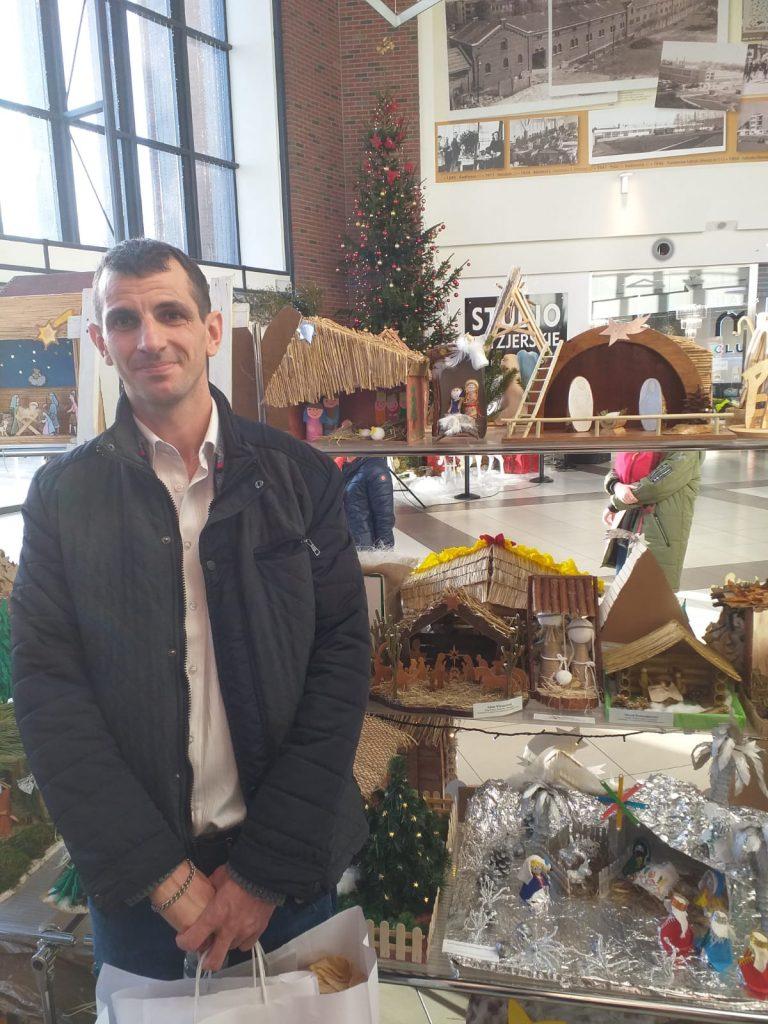Podopieczny DPS Rokocin w tle szopki Bożonarodzeniowe. W ręku trzyma otrzymane upominki za wyróżnienie w konkursie.