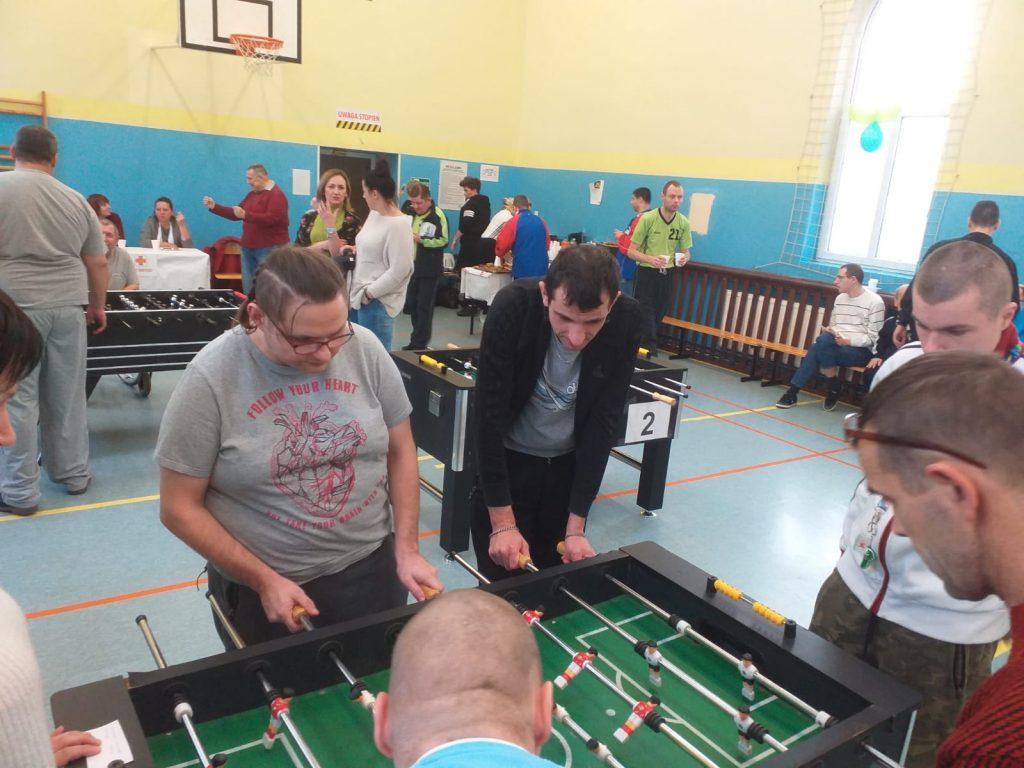Gracze rywalizują ze sobą podczas turnieju. W tle więcej osób oraz stołów do piłkarzyków.