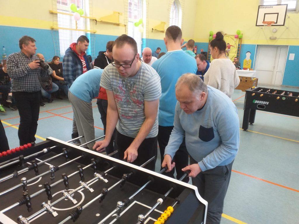 Skupieni mieszkańcy grający w piłkarzyki. W tle osoby przy innych stołach