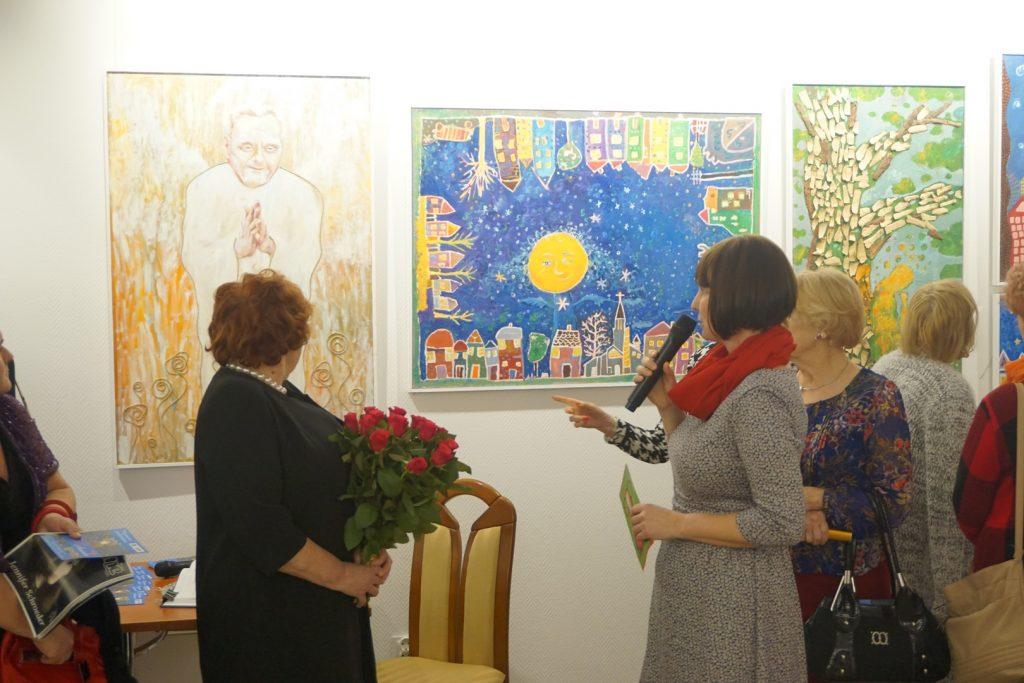 Pracownik DPS opowiada o kolorowych obrazach. Na obrazie jeden z mieszkańców DPS w obrazie anioła.