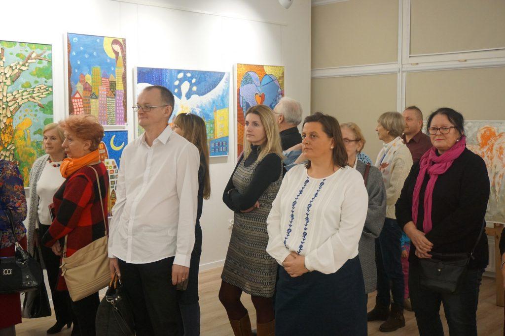 Grupa osób podczas oglądania wernisażu w tle kolorowe obrazy Aniołów w różnej interpretacji