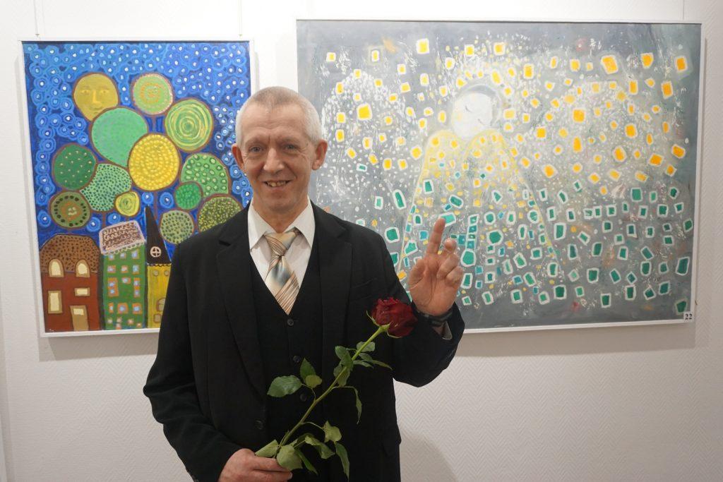 Autor obrazów a tle dwa kolorowe obrazy. W ręku trzyma róże.