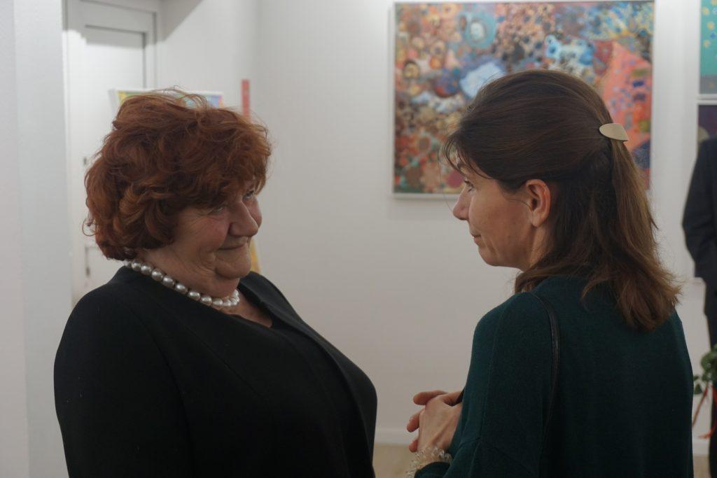Uśmiechnięta Dyrektor DPS rozmawia z kobietą podczas trwającej wystawy
