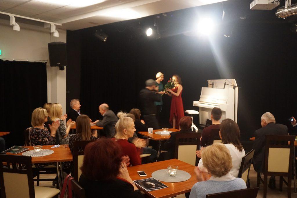 Gratulacje od dyrektora ODK dla artystki grającej na fortepianie.