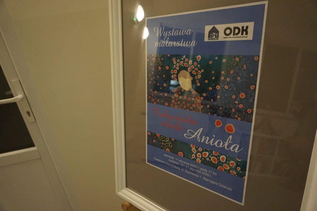 Plakat Wystawy Malarskiej Rokocińska Szkoła Anioła w białej ramce wisi na sztaludze.
