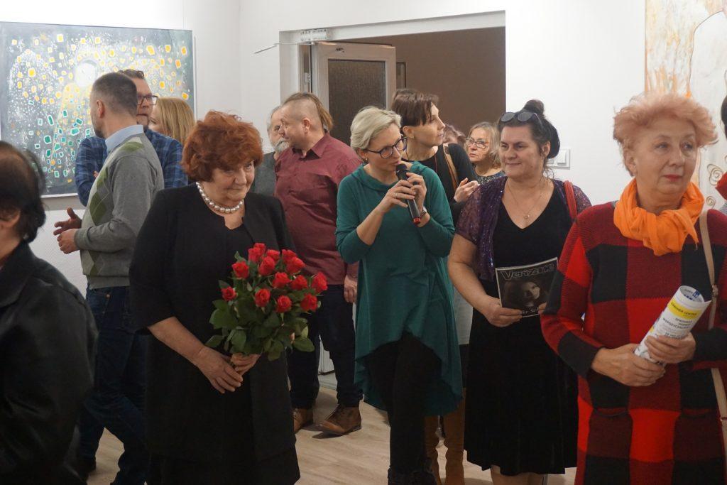 Dyrektor ODK z mikrofonem obok Dyrektor DPS trzymająca bukiet czerwonych róż w podziękowaniu. Wokół ludzie wchodzący na stalę.