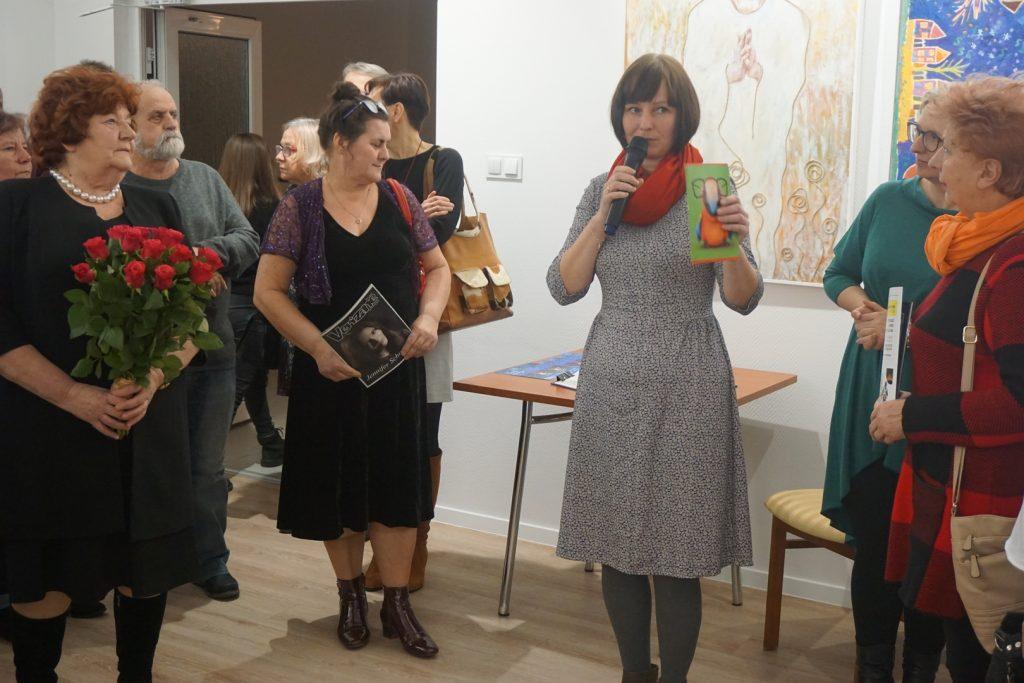 Pracownik DPS podczas przemówienia - wyjaśniała gościom intencje artystów oraz przebieg prac. Wokół ludzie oraz dyrektor DPS z bukietem róż.