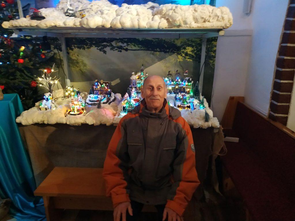 Uśmiechnięty mieszkaniec, a w tle szopka bożonarodzeniowa