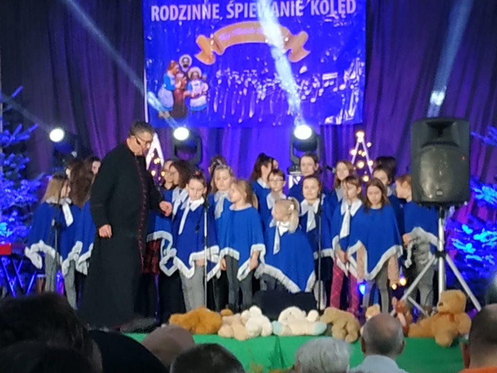 Grupa dzieci ubrana w niebieski ponczo stojąca na scenie obok nich ksiądz