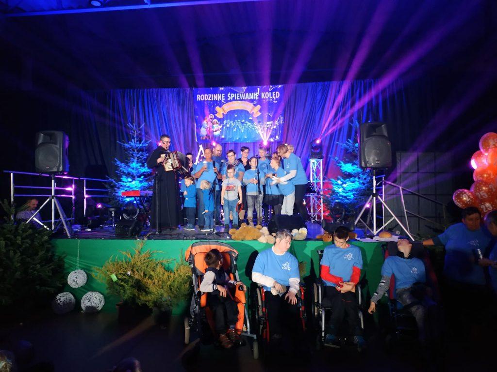 Występy na scenie przybyłych rodzin podczas kolędowania. Pod sceną 4 osoby na wózkach w tle światła i scena