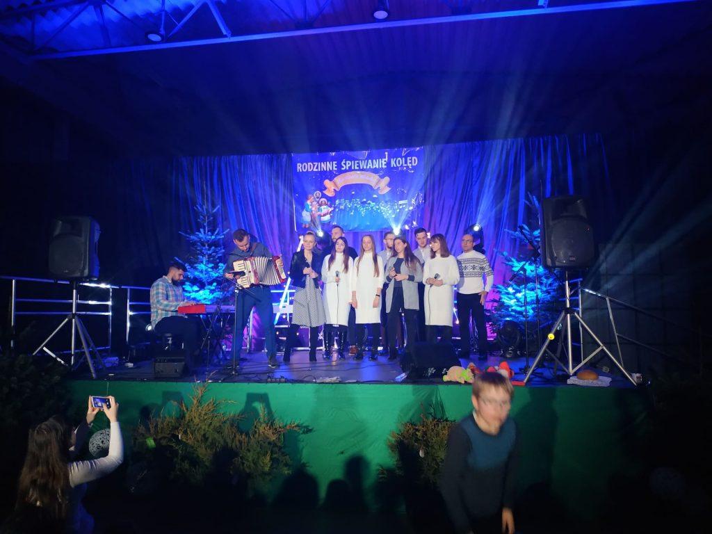 Występy rodzinne na scenie, grupa osób stojąca na scenie podczas śpiewania kolęd. Jedna z nich gra na akordeonie a druga na klawiszach