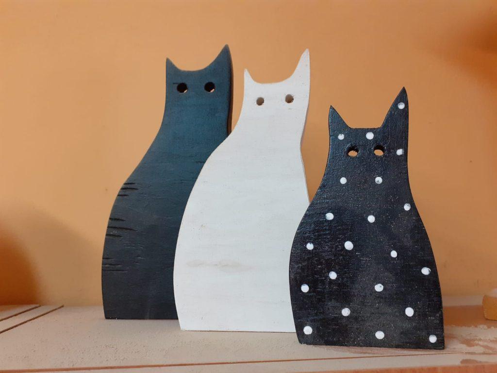 Trzy koty wykonane z drewna, czarny, biały oraz czarny w białe kropki
