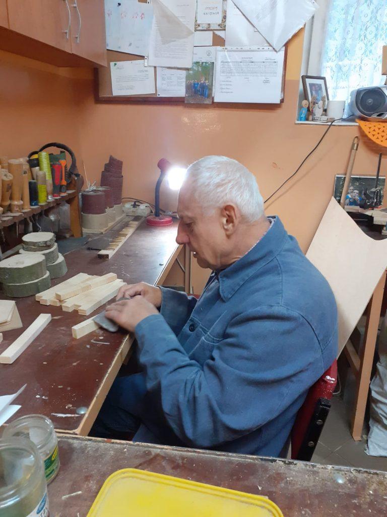 Mieszkaniec siedzi przy stole w pracowni, obok niego drewniane elementy, które szlifuje ręcznie