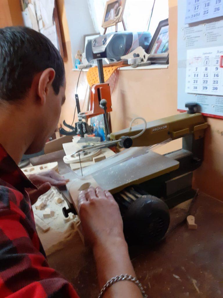 Mieszkaniec wycinający w maszynie kolejne wzory drewnianych elementów