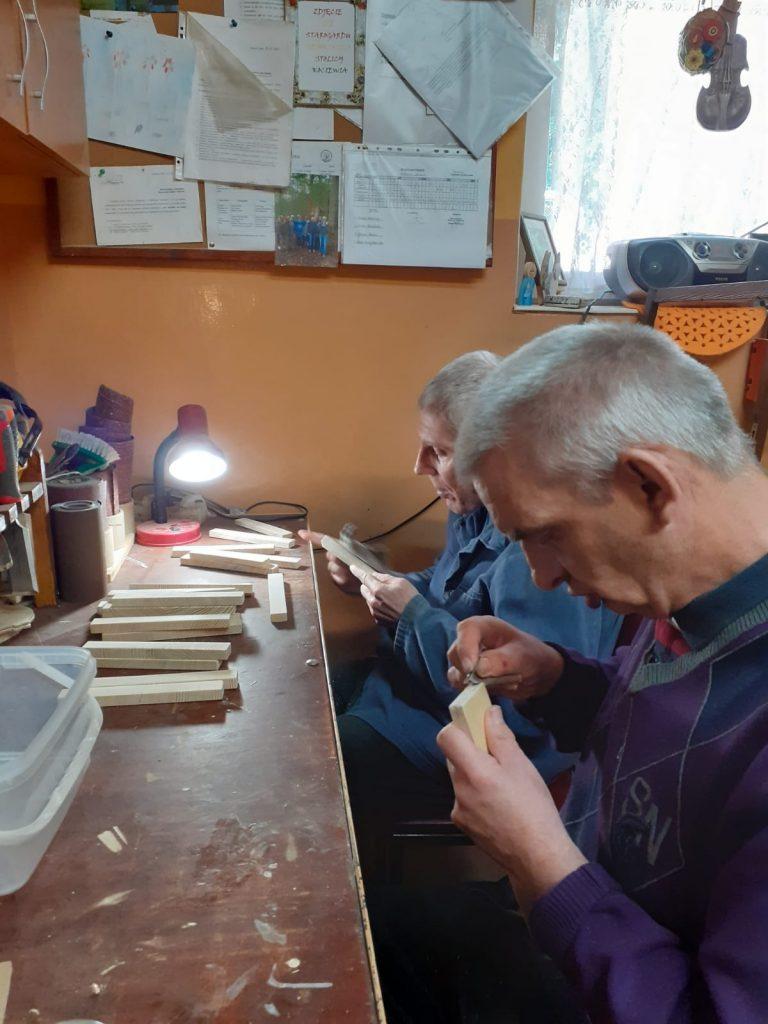 Dwóch podopiecznych siedzących w pracowni, szlifuje drewniane elementy