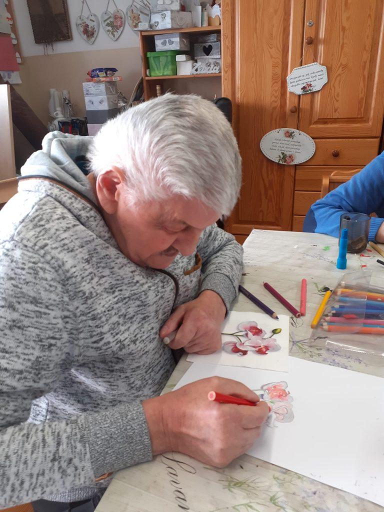 Podopieczny trenujący swój warsztat malarstwa, rysuje kredkami obraz