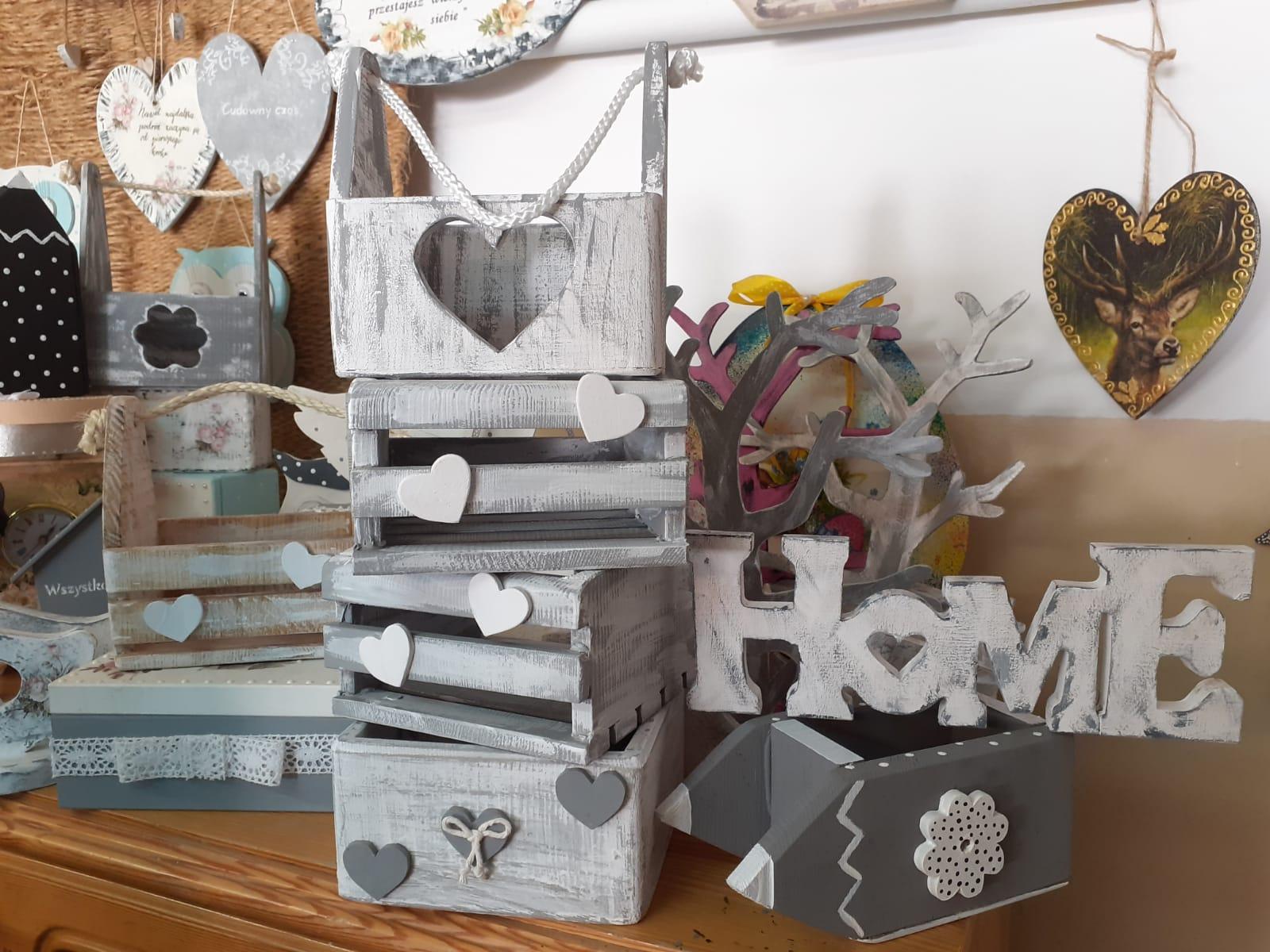 Kącik drewnianych skrzynek, napis Home, pudełeczka drewniane. Wszystko szaro białe z motywem serc