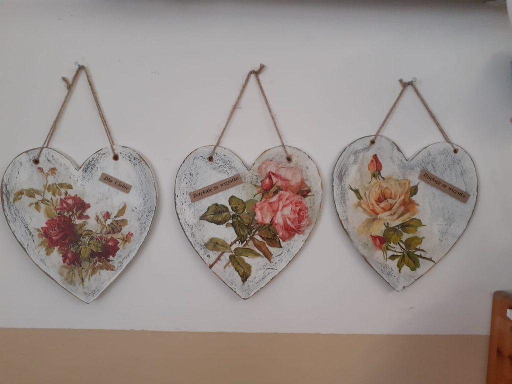 Trzy serca zawieszone na jutowym sznurku. W środku drewnianych serc przyklejone róże