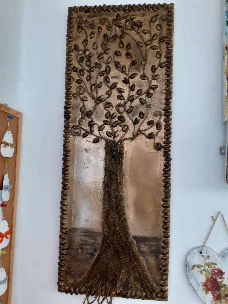 Obraz - drzewa ozdobiony drobnymi ciemnymi kamieniami wokół ramki. Liście wykonane z czarnego kamienia