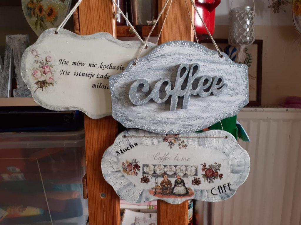 Drewniane zawieszki ozdobne, na nich cytaty oraz napis coffee