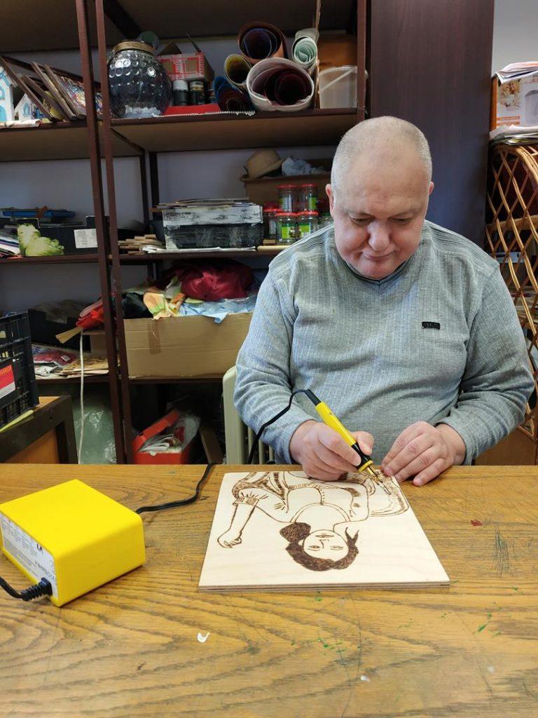 Podopieczny siedzi przy drewnianym stole i metodą wypalania w drewnianej sklejce maluje kobietę