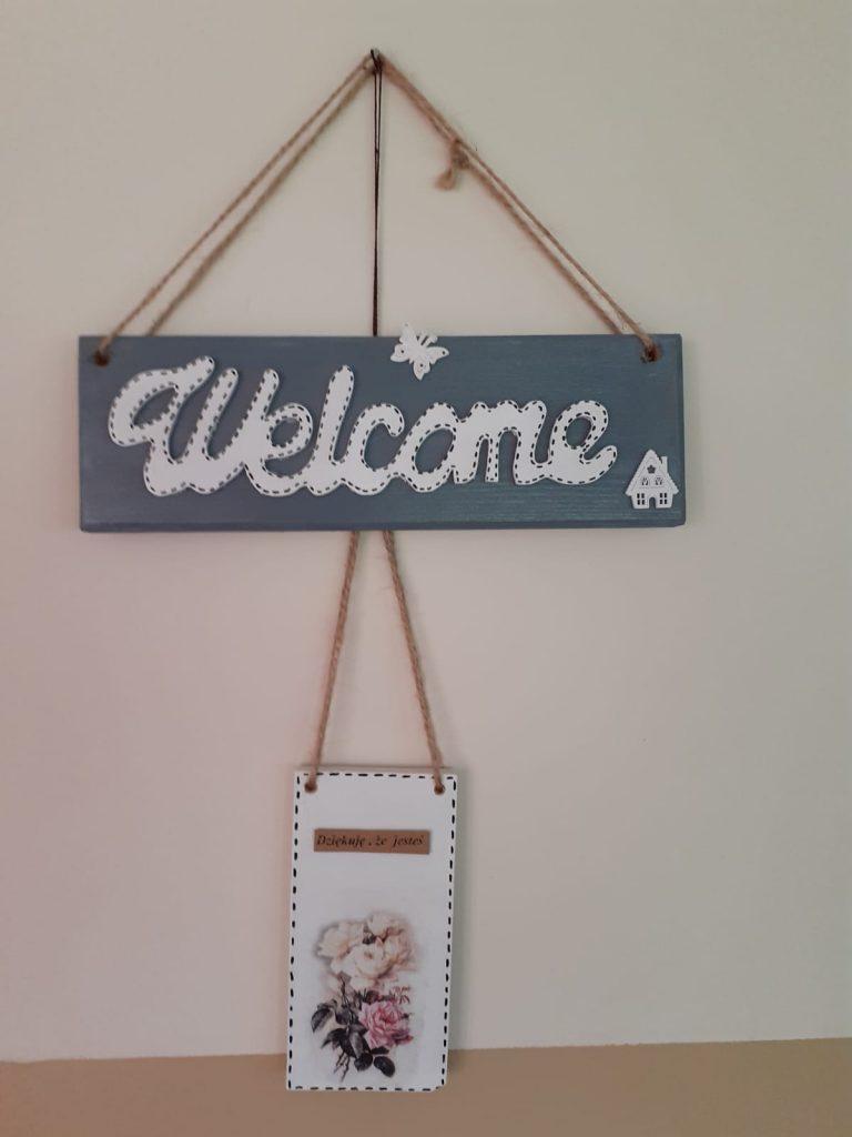 """Drewniane ozdoby """"Welcome"""" na ciemnym tle oraz zawieszka na drzwi z napisem dziękuję, że jesteś"""