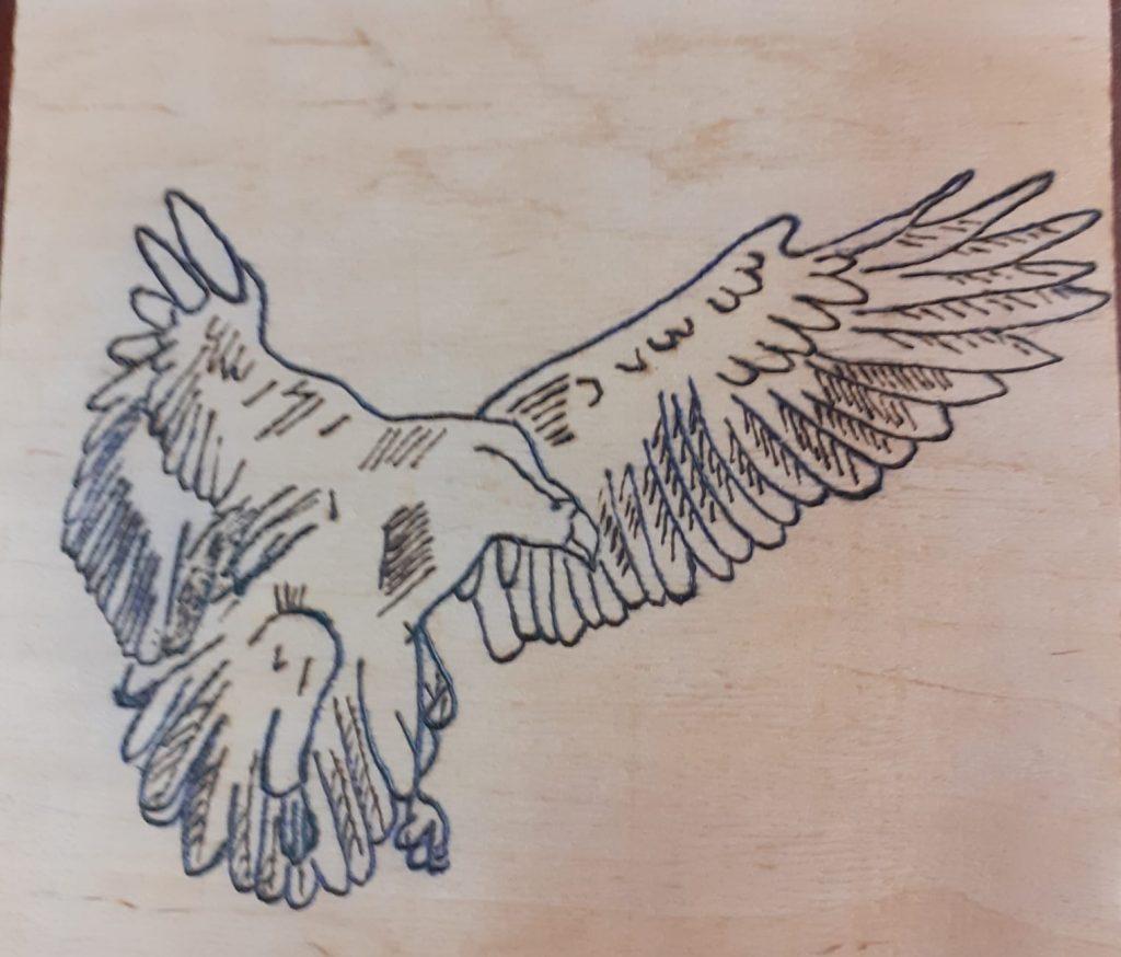 Wypalanka w drewnie przedstawia ptaka z rozłożonymi skrzydłami