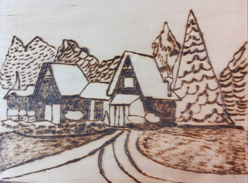 Wypalanka w drewnie przedstawiająca domki, choinki oraz drogę