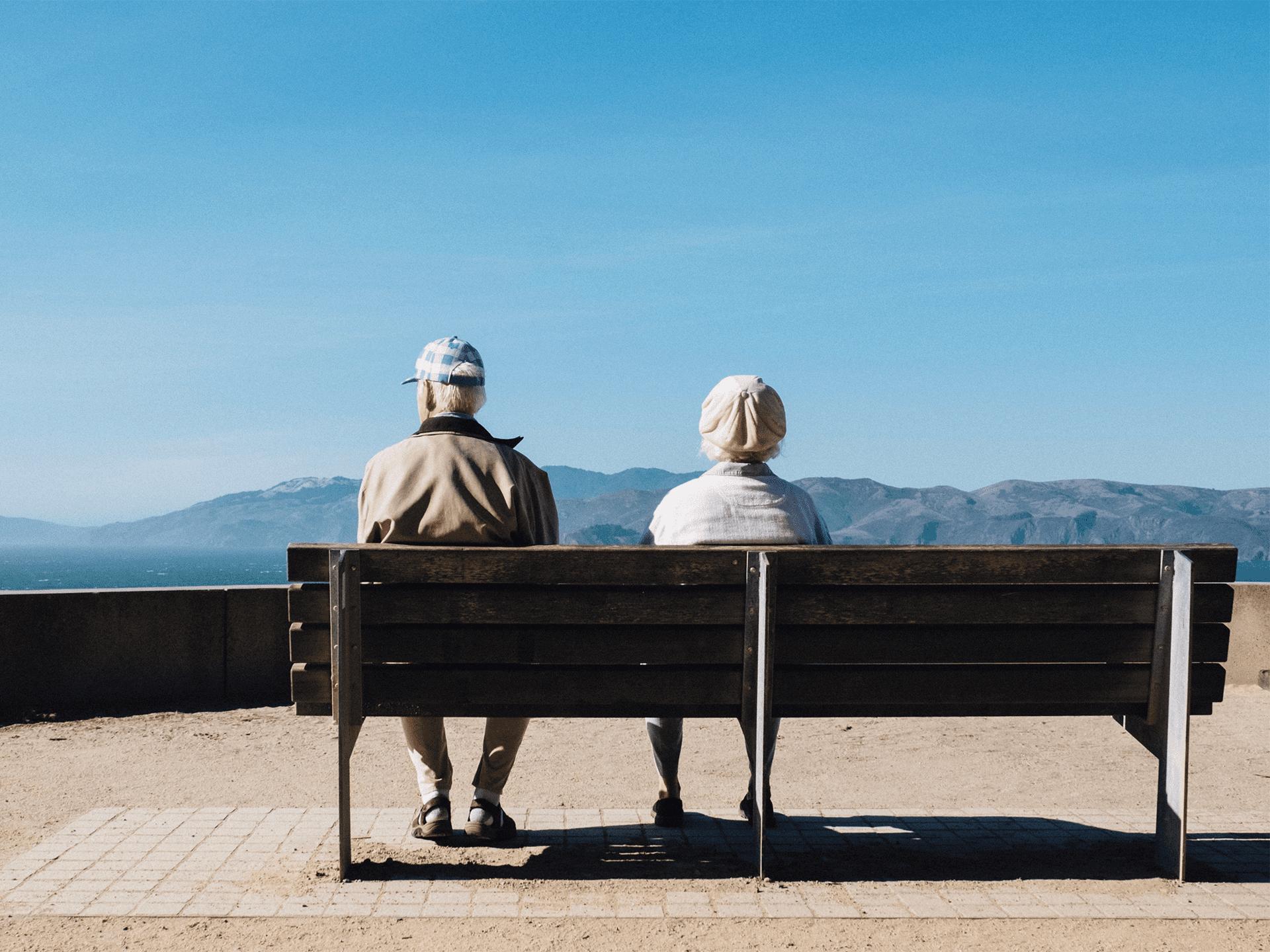 Dwie osoby siedzące obok siebie na drewnianej ławce, w tle góry i woda