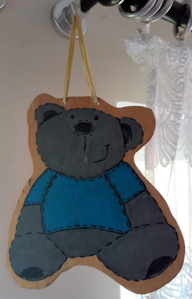 Drewniany niebieski miś - ozdoba wisząca na sznurku. Drewniana wisząca na sznurku ozdoba misia. Uśmiechnięty szary miś ubrany w niebieską koszulkę.