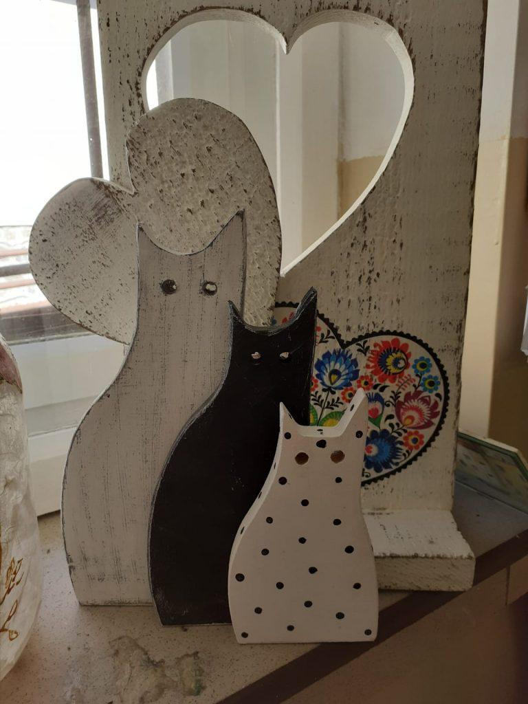 Trzy drewniane koty, jeden koloru drewna, drugi czarny, trzeci biały w czarne kropki.