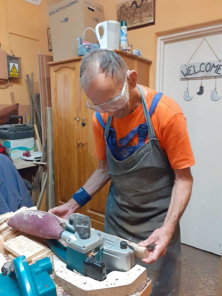 Mieszkaniec ubrany w okulary i fartuch ochronny stoi w warsztacie stolarskim i szlifuje drewniane elementy na szlifierce.