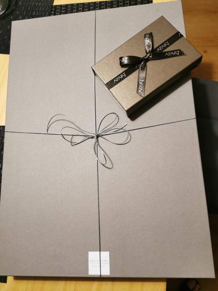 Zapakowany prezent w kartoniku tekturowym oraz mały prezencik w pudełeczku z napisem APART