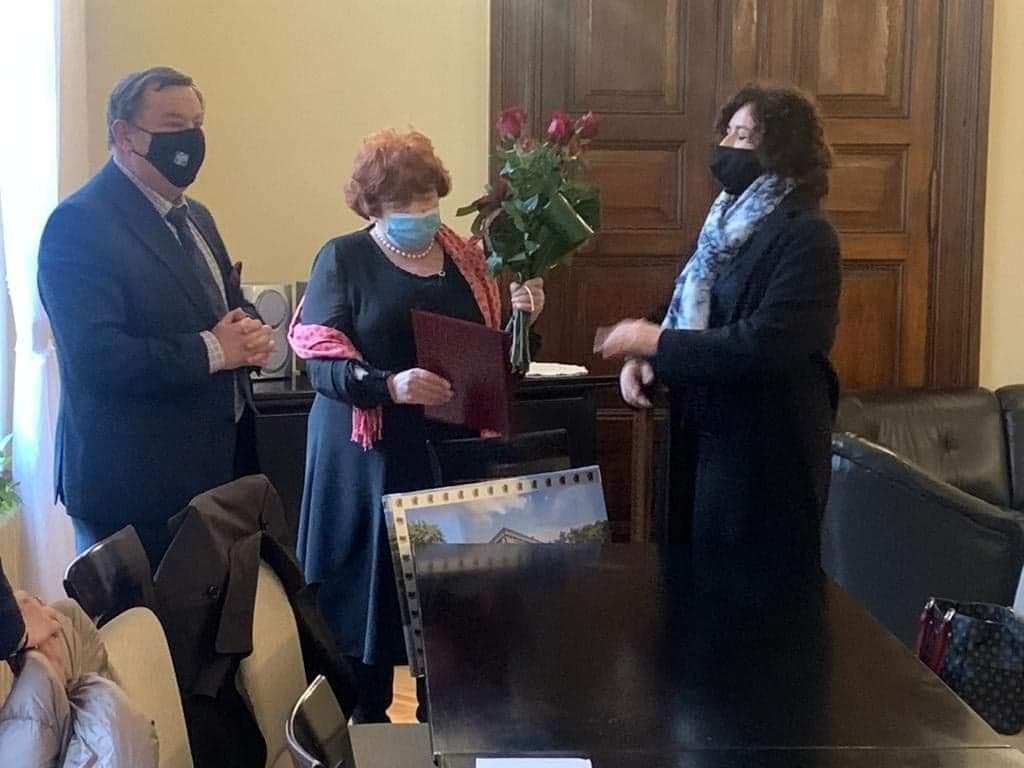 Dyrektor trzyma w ręku podziękowania oraz kwiaty obok stoi starosta oraz członek zarządu.