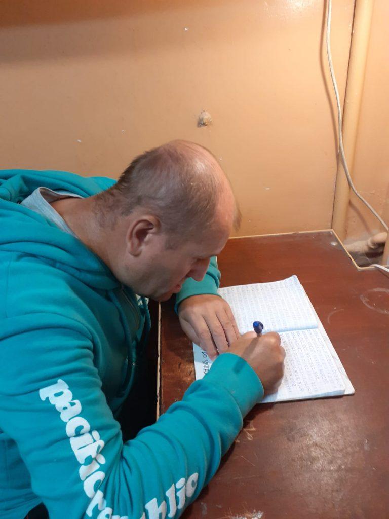Mężczyzna siedzący przy stole ćwiczący swoje pismo na warsztatach terapii zajęciowej