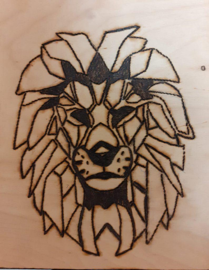 Drewniana wypalanka przedstawiająca twarz Lwa