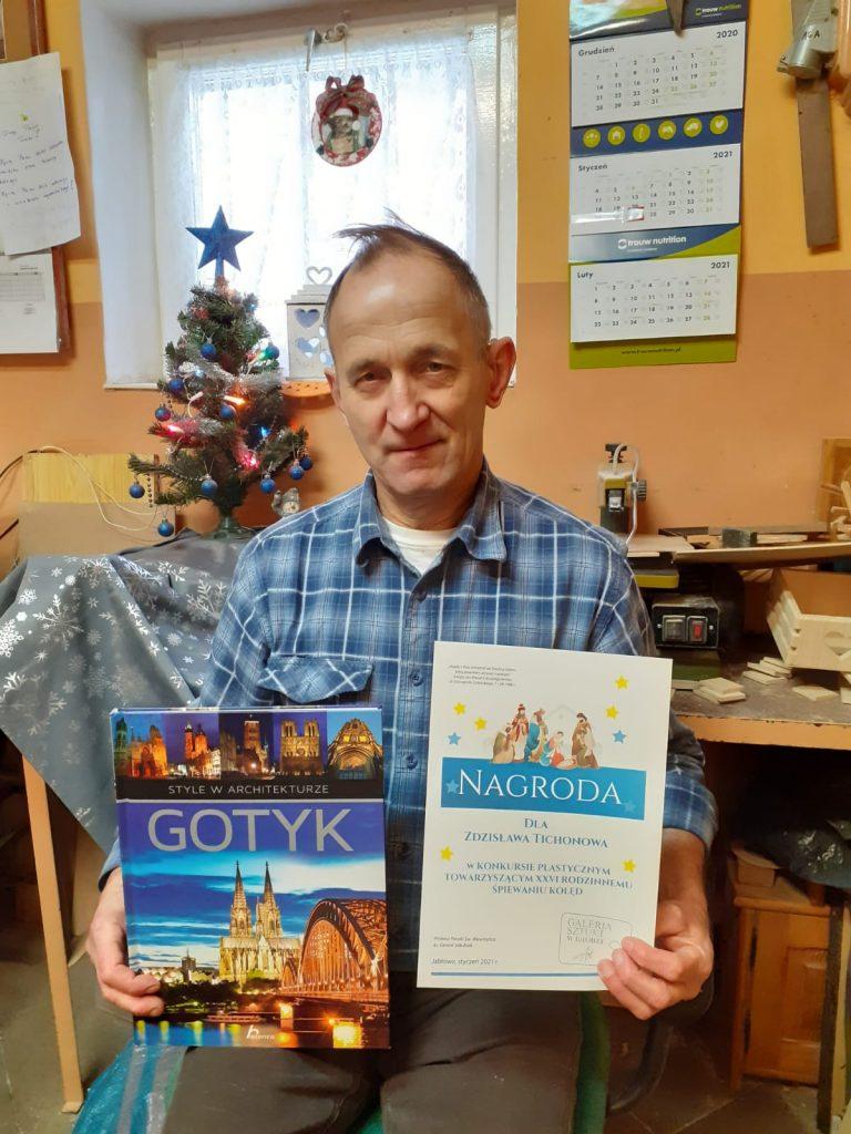 Mieszkaniec trzymający dyplom oraz książkę