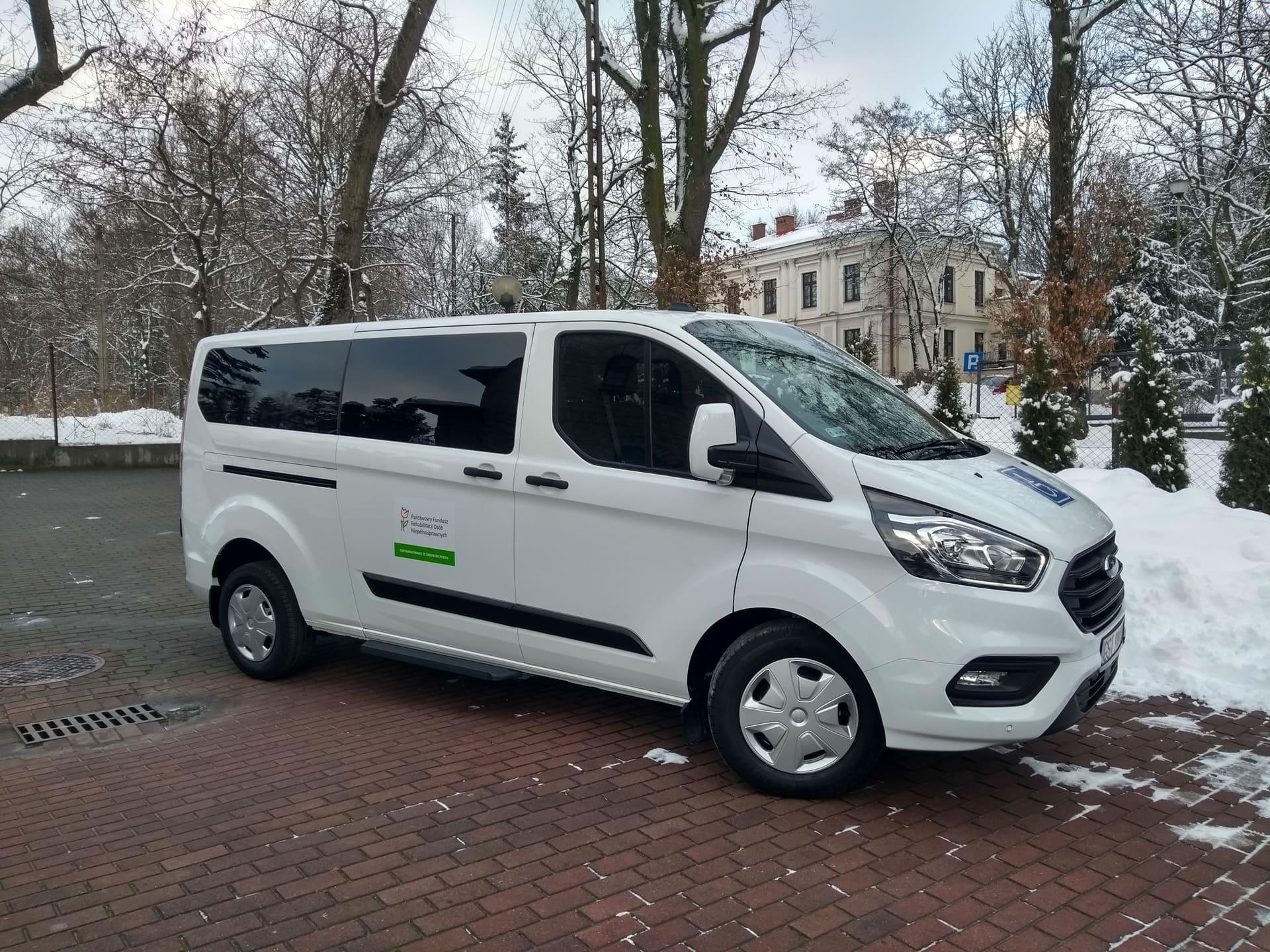 Duży biały samochód marki FORD z przyciemnianymi szybami z napisami dofinansowano ze środków PFRON. W tle pałac - główna siedziba DPS oraz drzewa