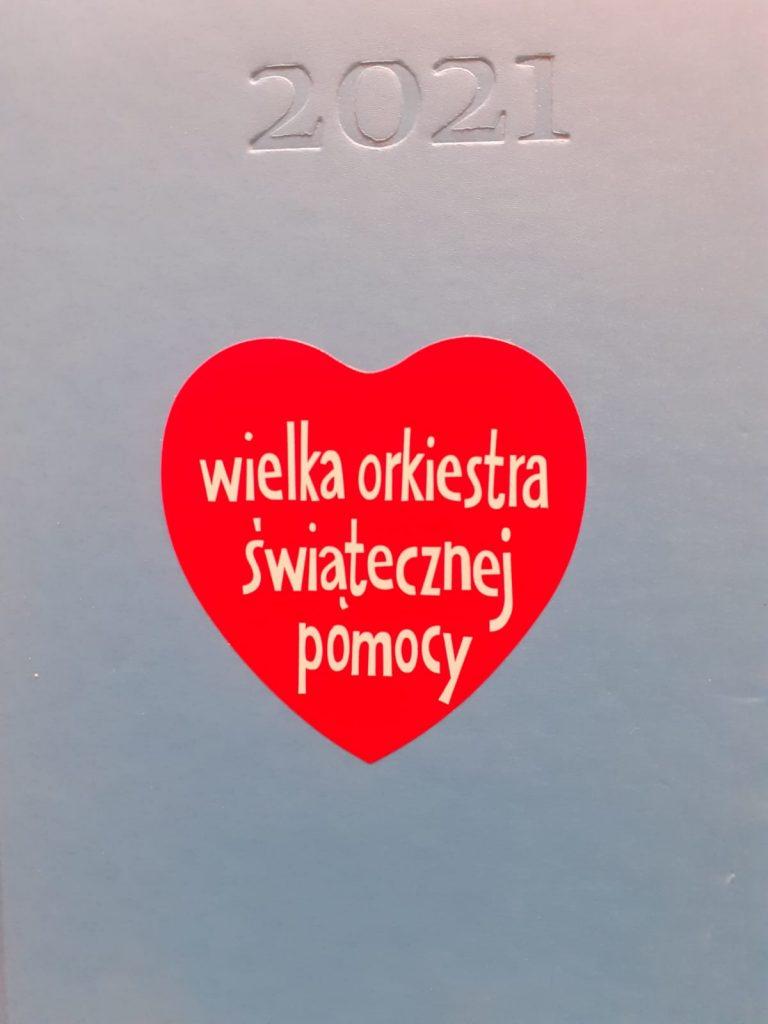 napis 2021 oraz czerwone serduszko z białym napisem Wielka orkiestra świątecznej pomocy