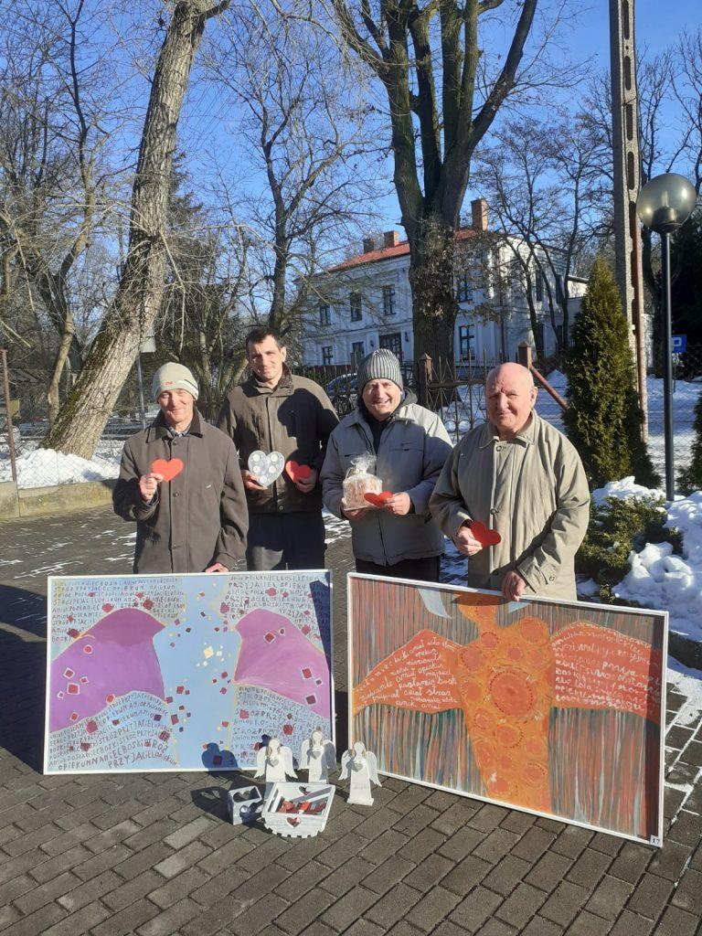 Czterech uśmiechniętych podopiecznych trzymających przedmioty na aukcję wielkiej orkiestry świątecznej pomocy, dwóch z nich przytrzymuje kolorowe obrazy aniołów. W tle drzewa oraz pałac
