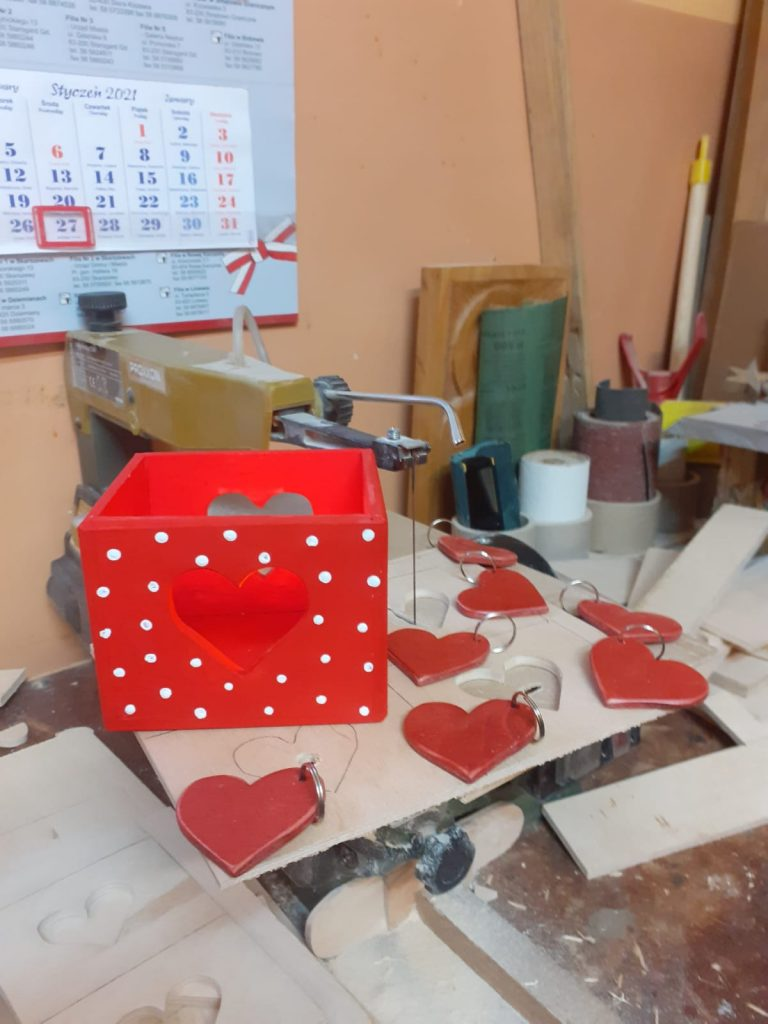 Ujęcie z warsztatu rzeźbiarskiego, na stole leżą czerwone serduszka (breloczki), obok czerwona skrzynka w białe kropki
