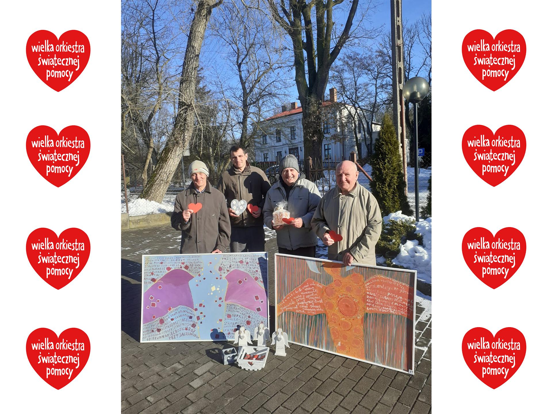Czterech uśmiechniętych podopiecznych trzymających przedmioty na aukcję wielkiej orkiestry świątecznej pomocy, dwóch z nich przytrzymuje kolorowe obrazy aniołów. W tle drzewa oraz pałac. W koło fotografii serduszka Wielkiej Orkiestry Świątecznej Pomocy