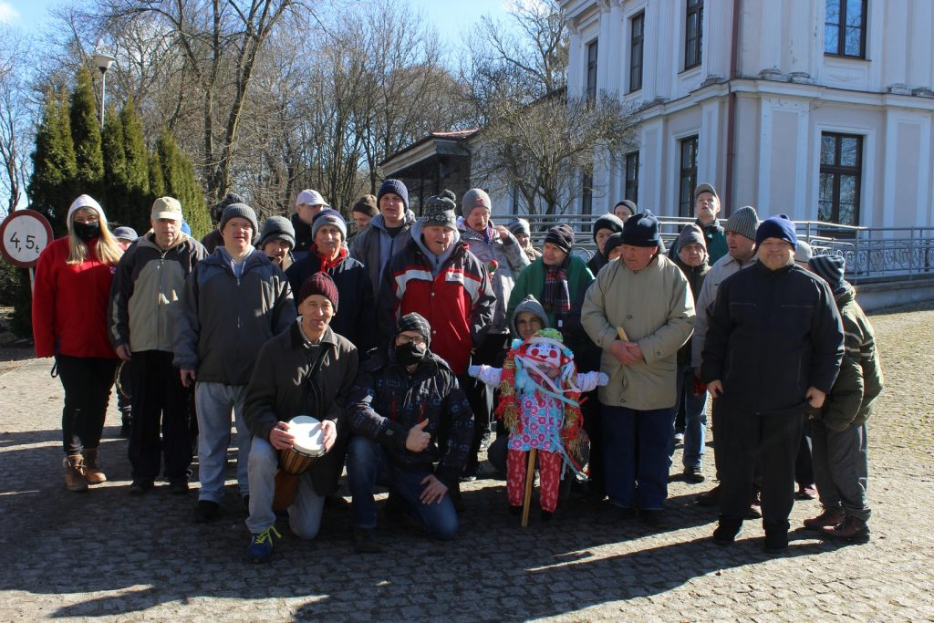 Grupa osób wraz z opiekunami, ubrana w kurtki czapki oraz gadżety muzyczne (tamburyno, grzechotka) w tle pałac, który jest główną siedzibą.