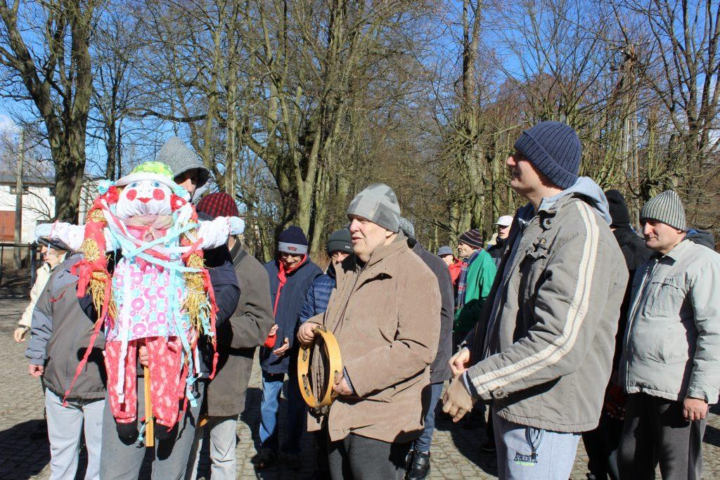 Grupa mieszkańców, ubrana w kurtki i czapki, jeden z nich trzyma tamburyno a drugi marzannę. W tle drzewa