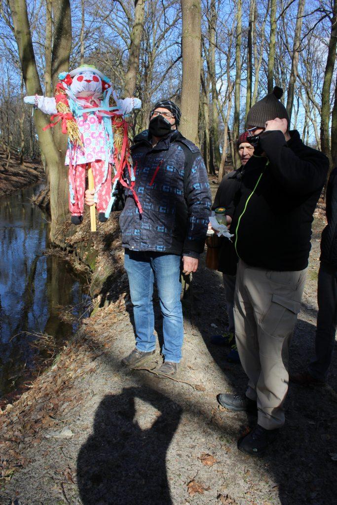 Dwóch meżczyzn stojących obok rzeczki. Jeden z nich trzyma w rękach marzannę.