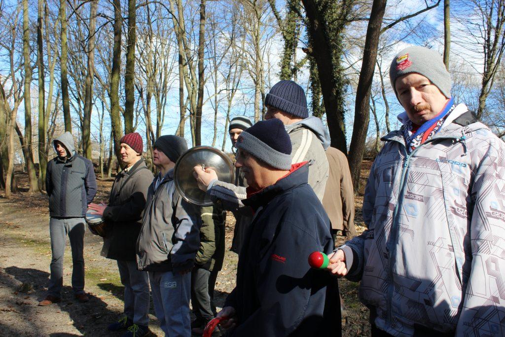 Grupa mieszkańców stoi i spogląda przed siebie, jeden z podopiecznych spogląda w stronę kamery w ręce trzyma grzechotkę.