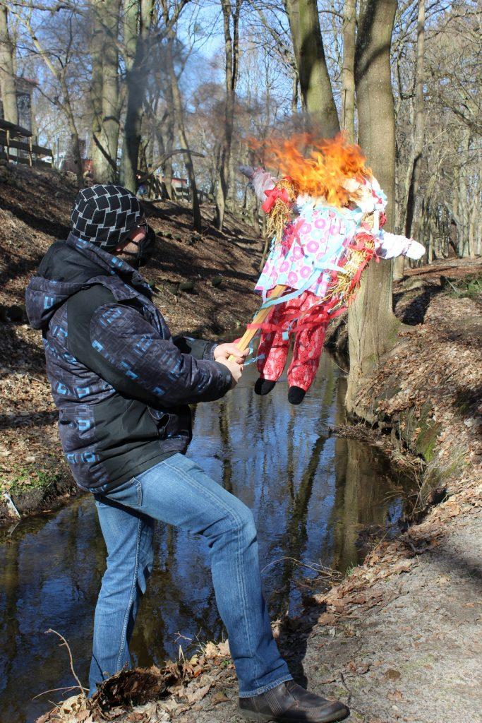 Instruktor trzyma w ręce palącą się marzannę