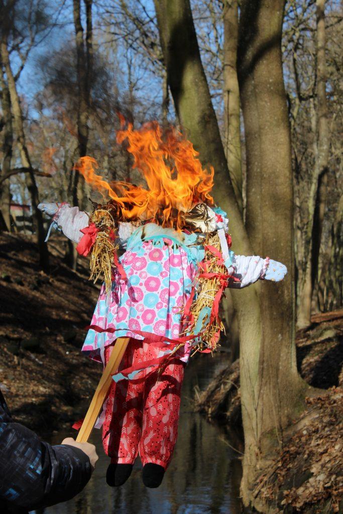 Zbliżenie na palącą się marzannę w tle drzewa oraz rzeczka