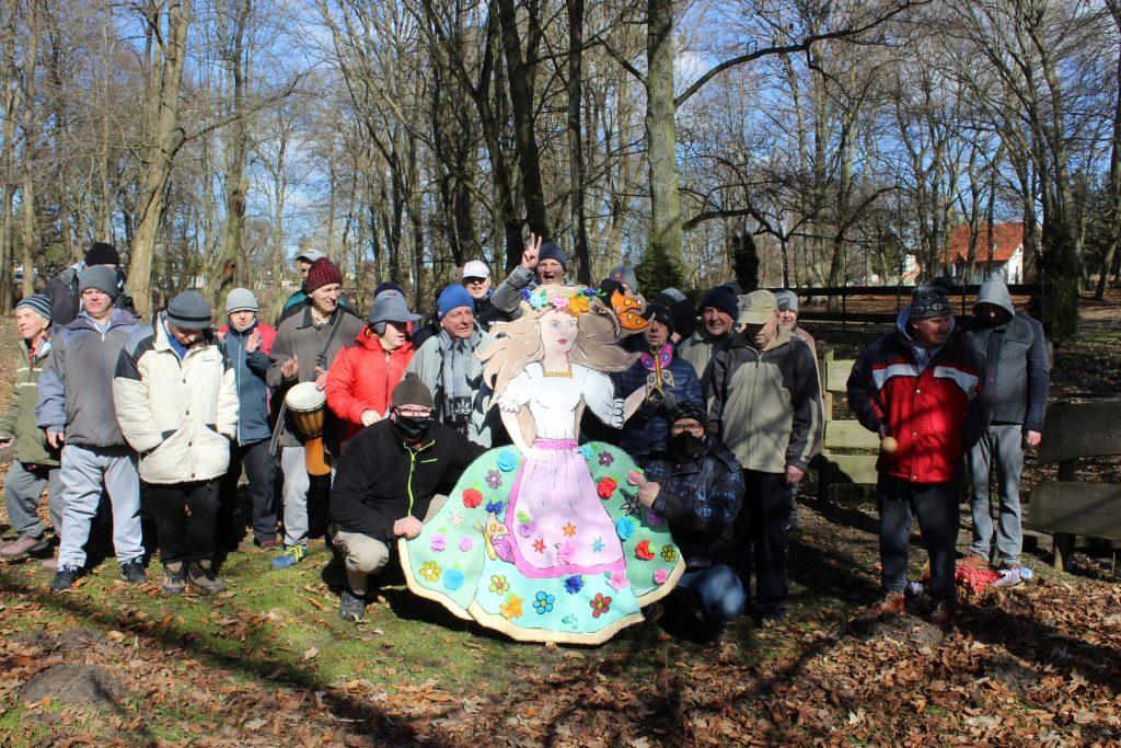 Grupa mieszkańców stojących w parku, przed nimi postać marzanny z kartonu, która trzymają opiekunowie grupy